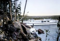 Visitor sitting on the shore of Yellowstone Lake with boat in water Photo