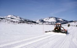 Snow grooming maching on the road at Swan Lake Flats Photo
