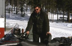 Maintenance worker filling snowmobile with fuel Photo