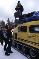 Bellman & snowcoach drivers unloading snowcoach at Old Faithful Snow Lodge Photo