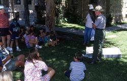 Sabrina Trusk giving an interpretive talk on the lawn outside of the Albright Visitor Center at Mammoth Hot Springs Photo