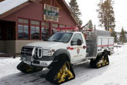 Fire engine equipped with Mattracks in front of Old Faithful Snow Lodge Photo