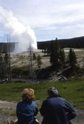 Visitors watching Old Faithful eruption from Firehole River Photo