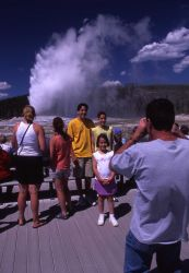 Visitors getting picture taken at Old Faithful geyser Photo