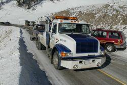 Tow truck towing damaged SUV east of Phantom Lake Photo