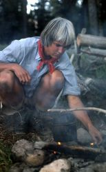 Woman tending campfire at backcountry campsite Photo