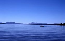 Boat on Yellowstone Lake with the Red Mountains in distance Photo