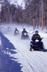 Snowmobiles on Madison/West entrance road in the winter Photo