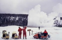 Snowmobiles & Old Faithful geyser in winter Photo