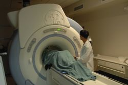 Technician checks MRI machine with patient Photo